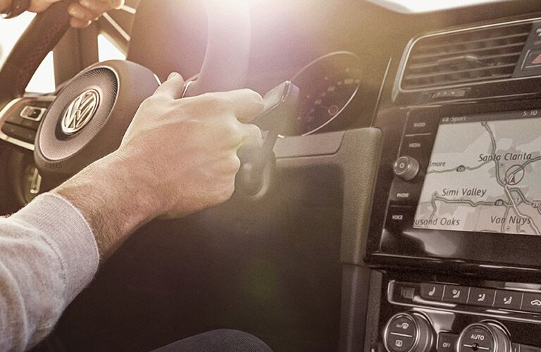 Infotainment, steering wheel, and dash of a 2019 Volkswagen Golf GTI. Human hands grip the wheel, while navigation displays on the infotainment.