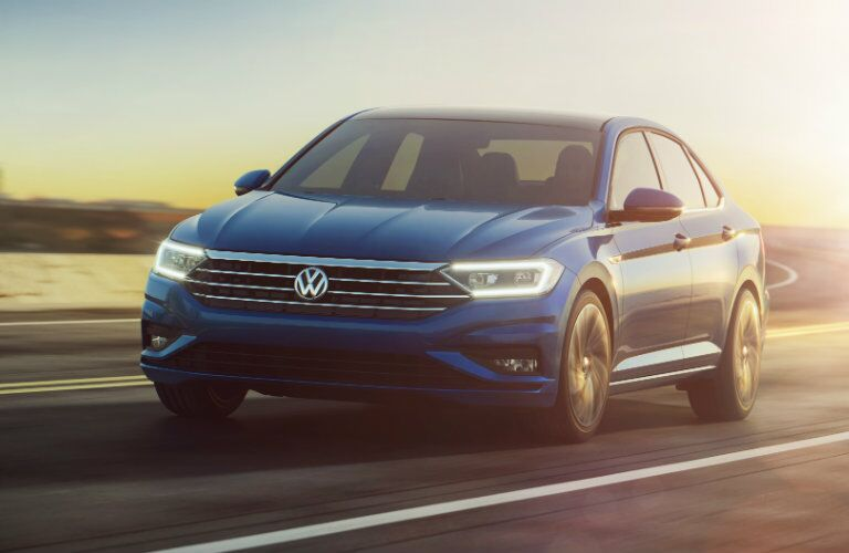 Blue 2019 Volkswagen Jetta drives down a highway in the desert with the sunlight enveloping the vehicle. Exterior front-angled view.