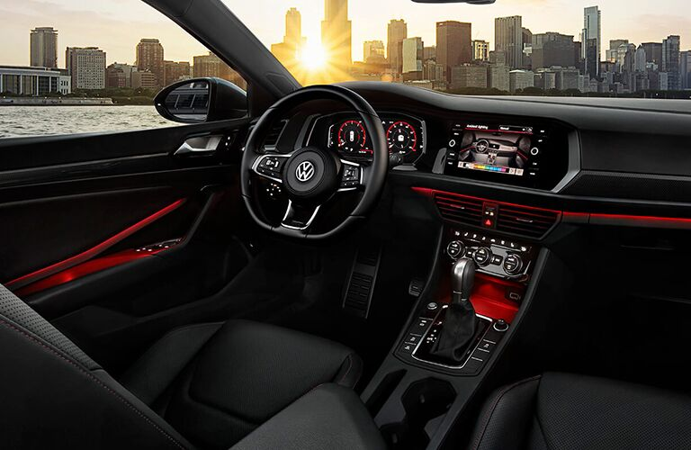 Interior front view of a 2019 Volkswagen Jetta GLI, showcasing the spiffy cockpit and driver's seat, lit by red ambient interior lighting. A city skyline is visible through the windows.