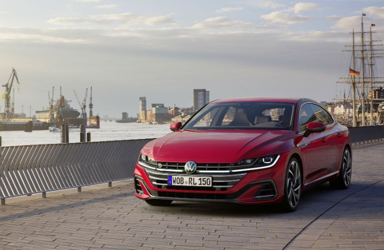 A head-on photo of the 2021 Volkswagen Arteon parked by some ships.