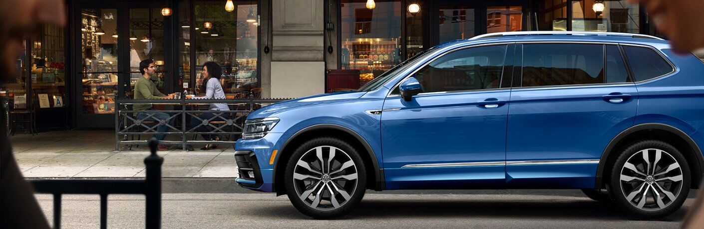 A left profile photo of the 2020 Volkswagen Tiguan parked on the side of the road.