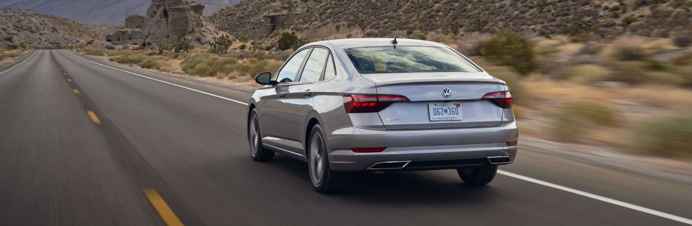 A rear photo of the 2021 Volkswagen Jetta in motion on the road.