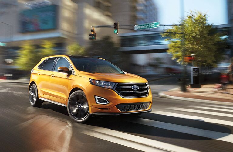 orange 2016 Ford Edge driving in city