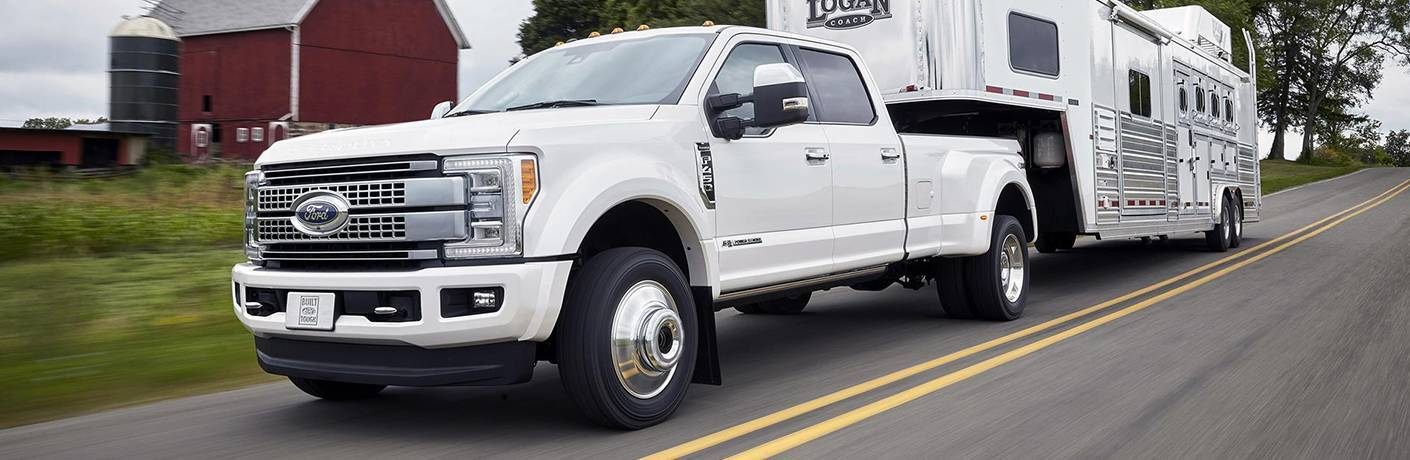 white Ford Super Duty pickup truck towing trailer