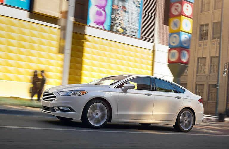 white 2017 Ford Fusion driving down street