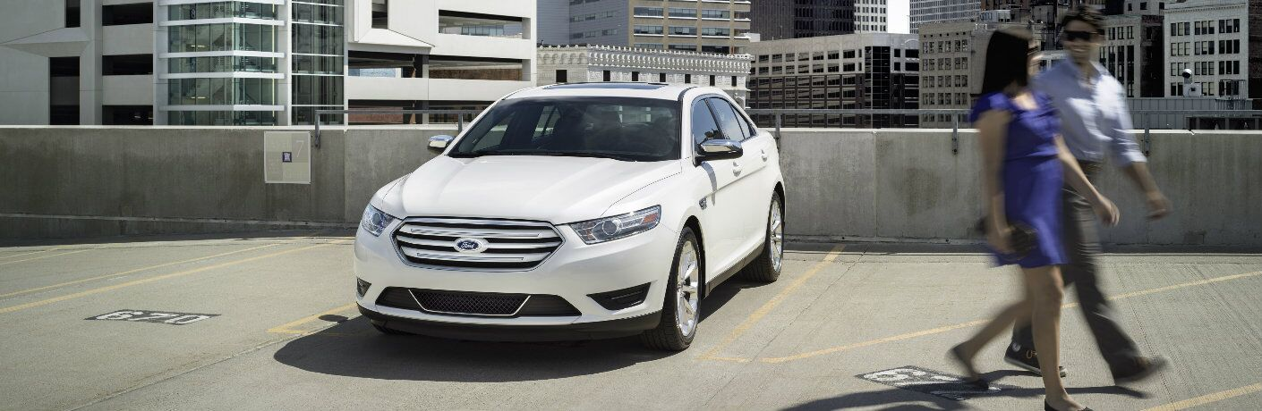 couple walking away from parked white 2017 Ford Taurus