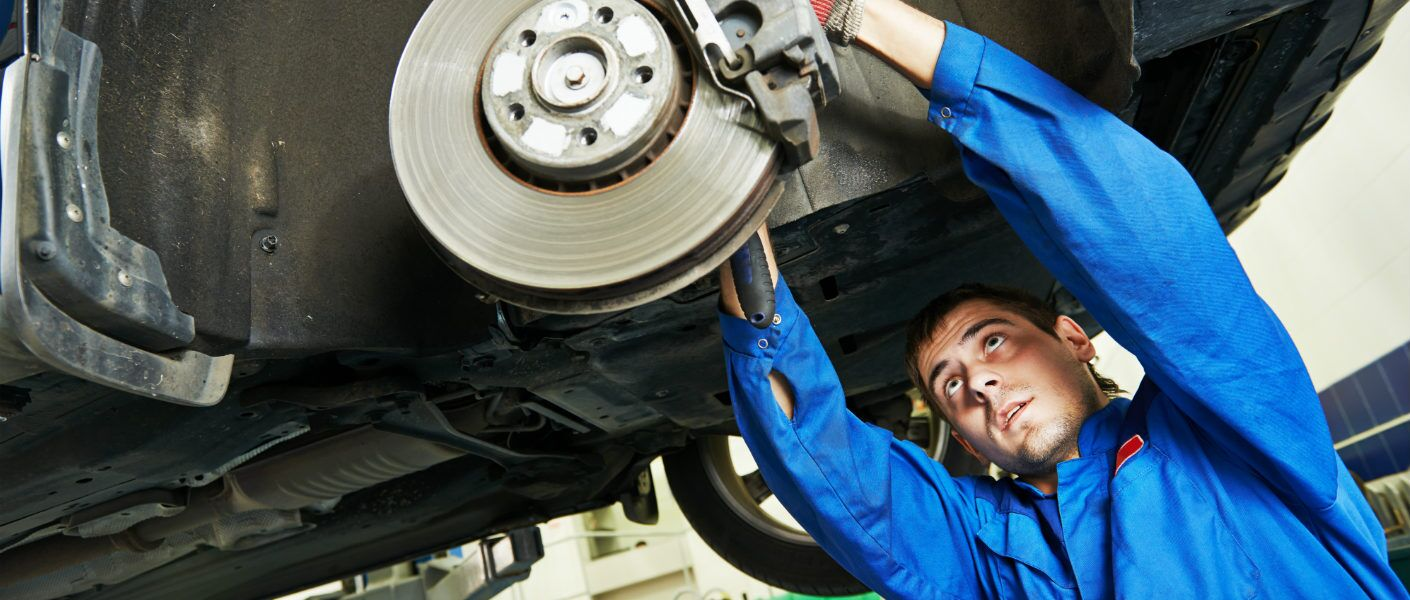 auto mechanic fixing brakes on a car