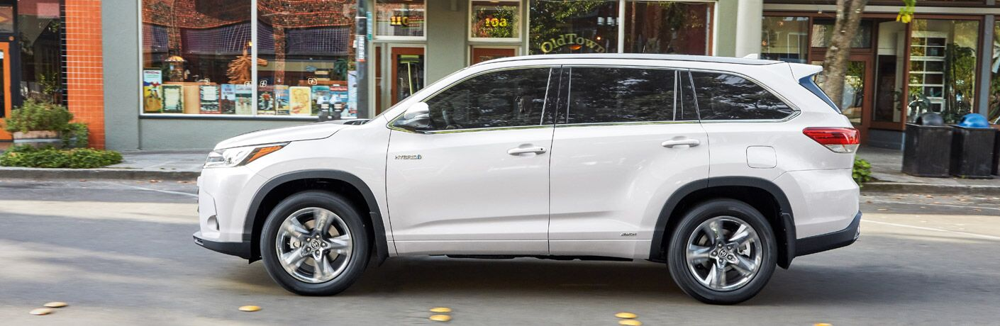2018 Toyota Highlander Hybrid in white parked in front of a storefront