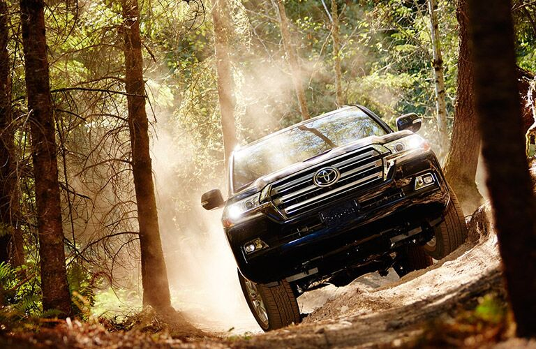 2018 Toyota Land Cruiser driving on an uneven path in the woods