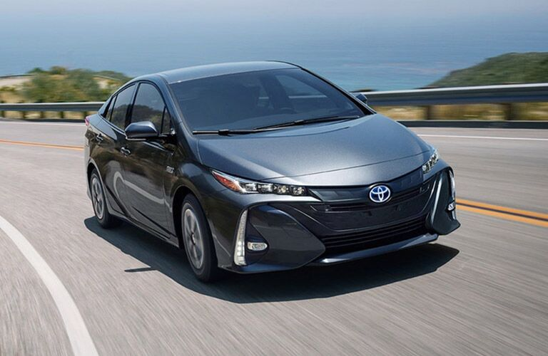 2018 Toyota Prius Prime in grey driving around a large bend in the road