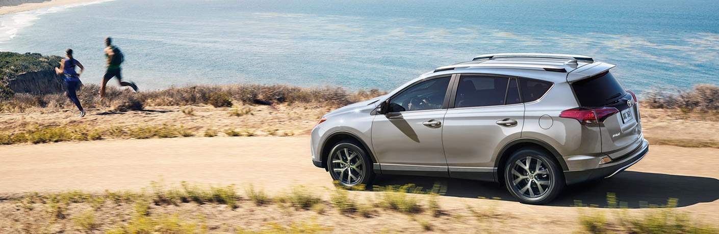 2018 Toyota RAV4 Hybrid in silver parked on a path near the ocean