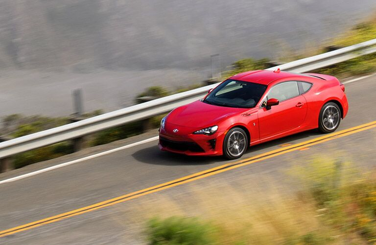 2019 Toyota 86 in red driving on a waterfront street