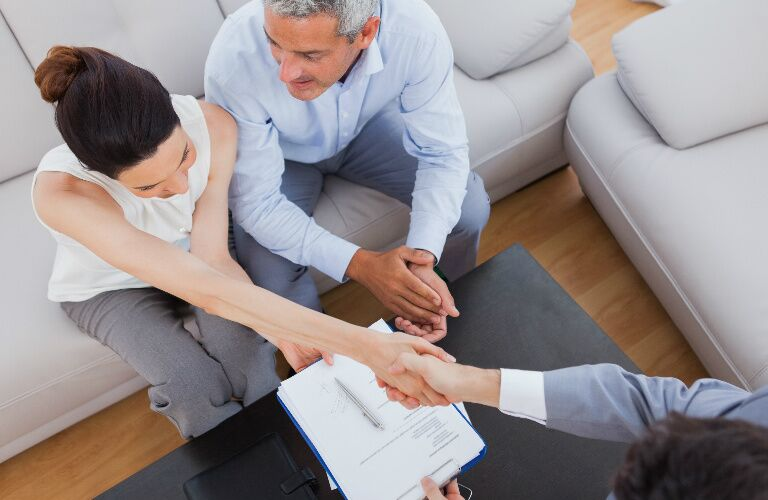 Couple shaking hands with an employee over paperwork