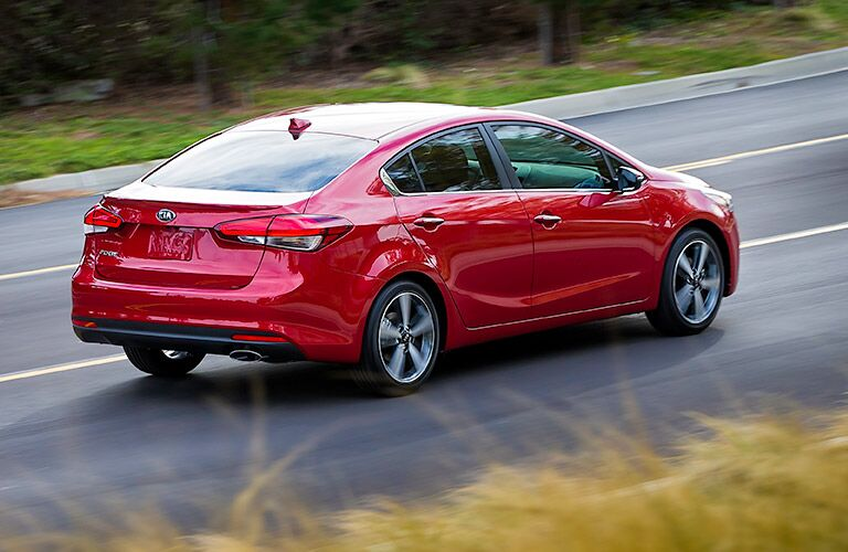 red kia forte driving on road
