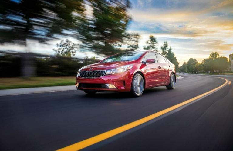 red kia forte driving fast down road