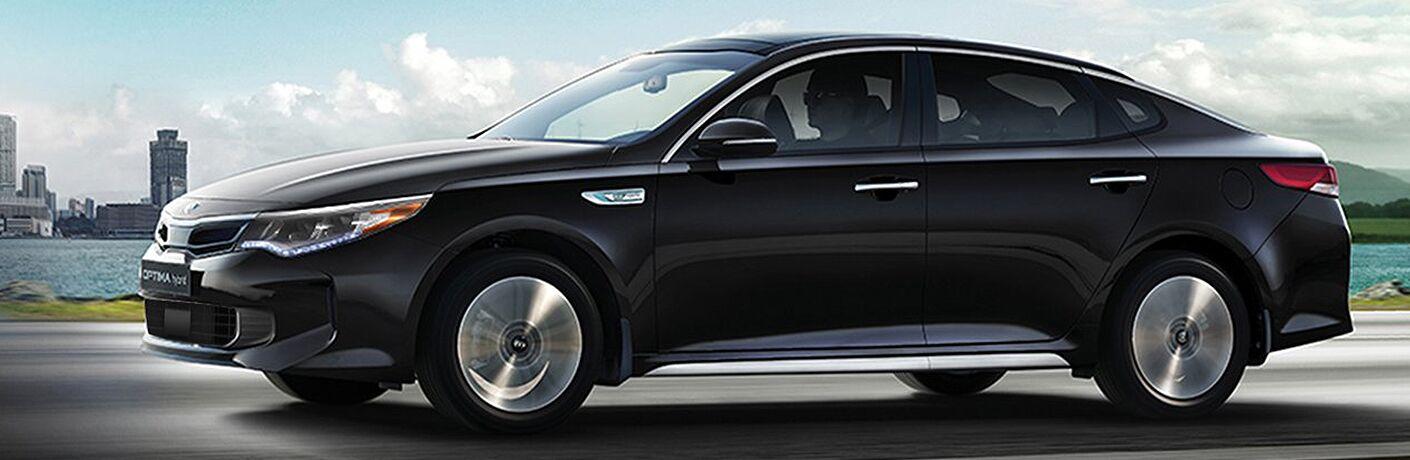 black kia optima hybrid driving by water