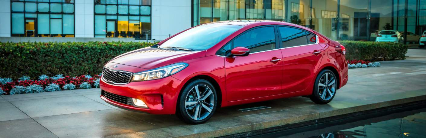 red kia forte parked outside building