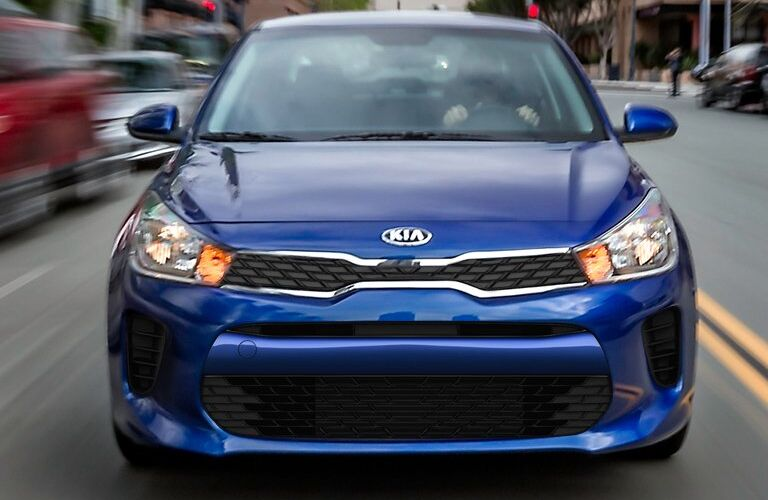 front view of blue kia rio on street
