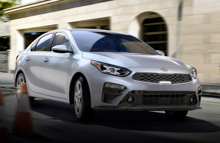 The front and side view of a moving 2020 Kia Forte.