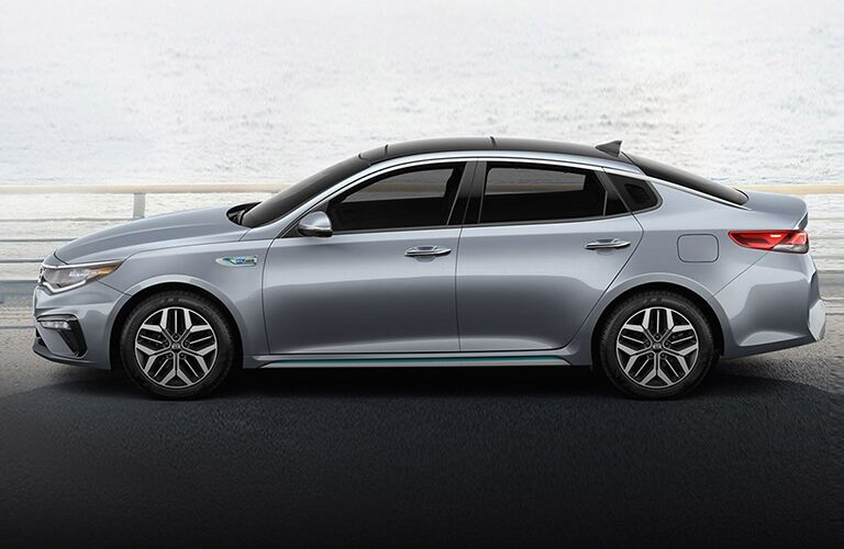 2020 Kia Optima Hybrid silver exterior driver side in front of body of water