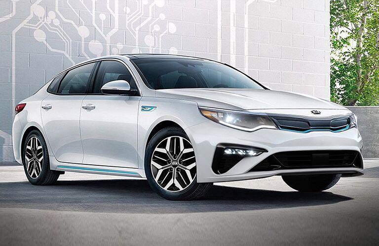 2020 Kia Optima Hybrid white exterior front fascia passenger side in front of white wall