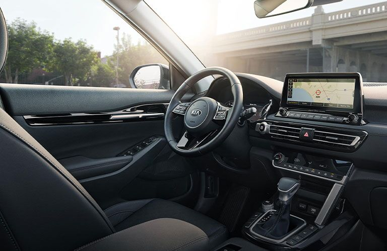 The front interior view of the center console and steering wheel of a 2021 Kia Seltos.