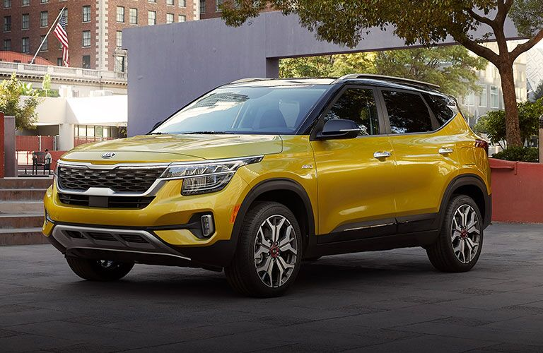 The front and side view of a yellow 2021 Kia Seltos parked in a park.