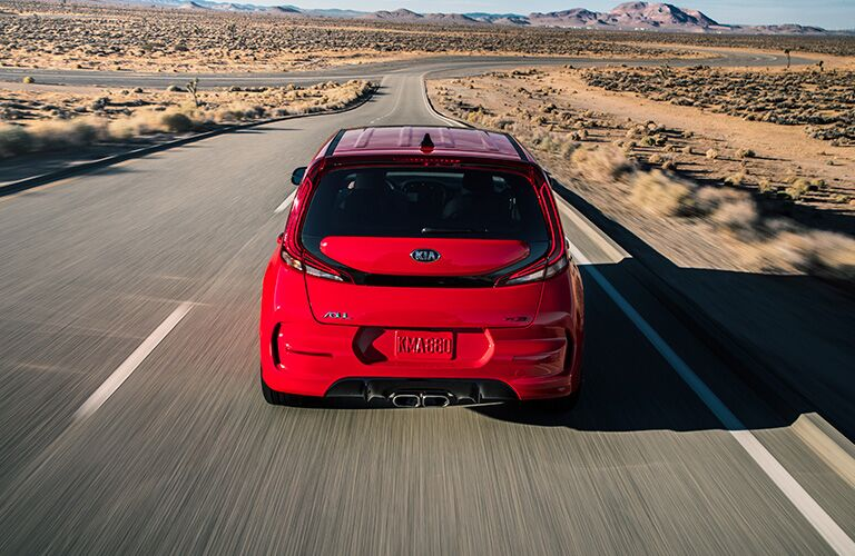 The rear image of a red 2020 Kia Soul driving down an open road.