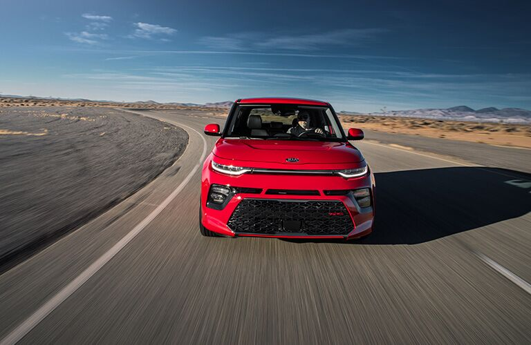 The front image of a red 2020 Kia Soul driving down an open road.