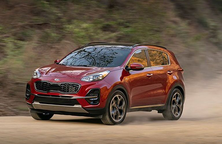 front left view of red kia sportage on dirt road