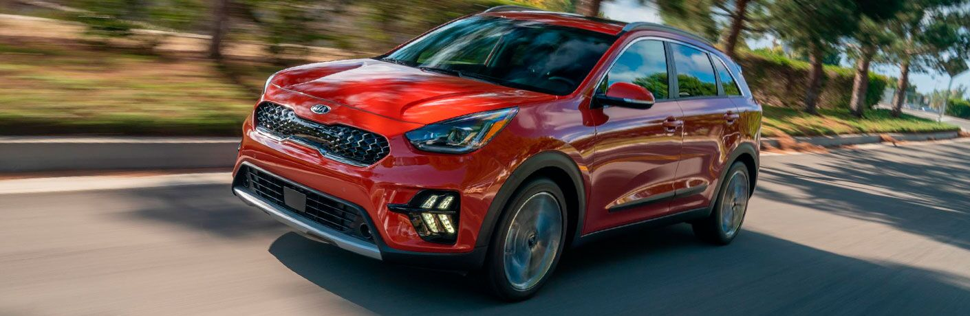 The front and side view of a red 2020 Kia Niro driving down an open road.