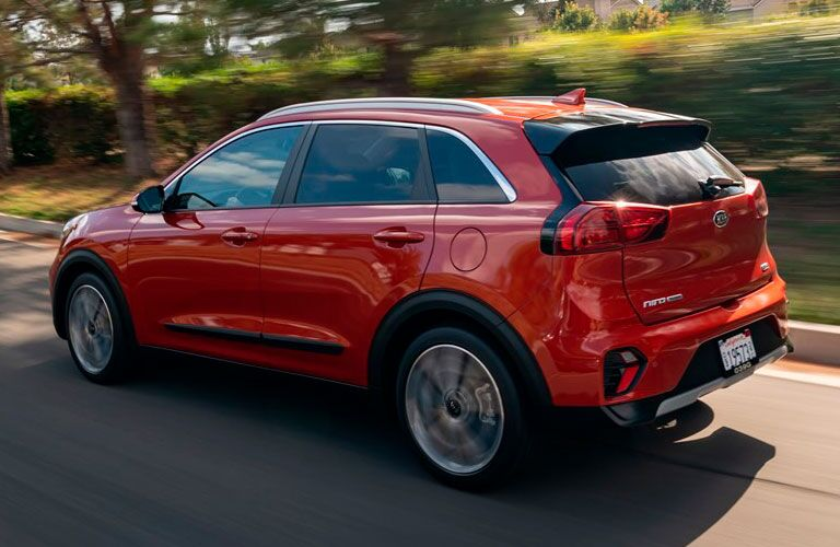 The side and rear image of a red 2020 Kia Niro driving down a road.