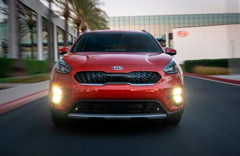 The front side of a red 2020 Kia Niro driving down a road.
