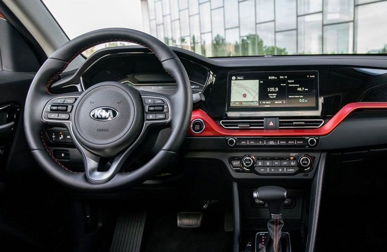 The front interior view of the steering wheel and center console inside a 2020 Kia Niro.