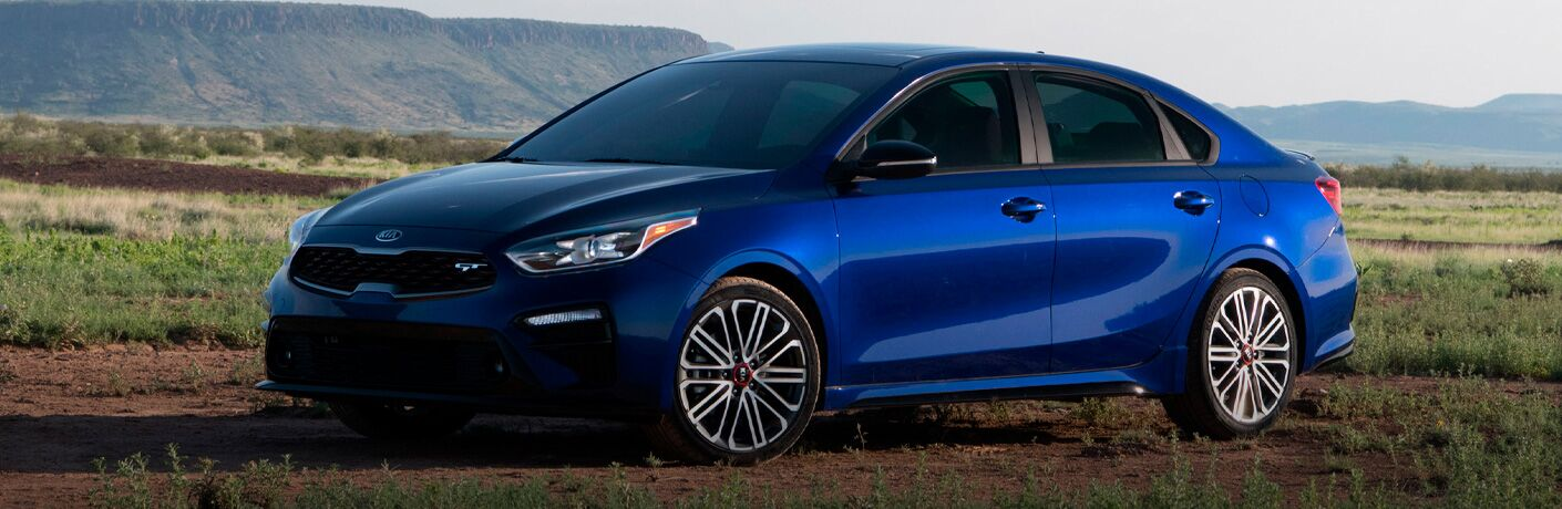 The front and side view of a blue 2021 Kia Forte driving on a rough road.