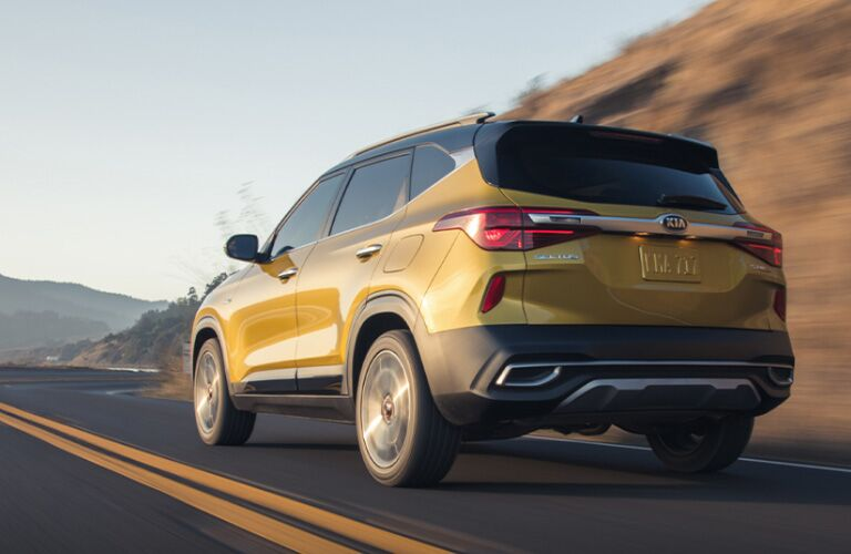 The rear side view of a yellow 2021 Kia Seltos driving down a road.