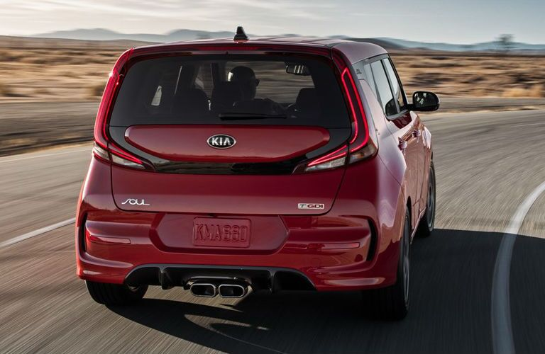 The rear view of a red 2021 Kia Soul driving down a road.