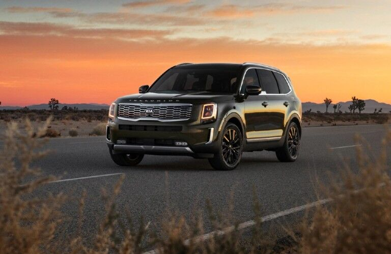 The front view of a dark green 2021 Kia Telluride driving during sunset.