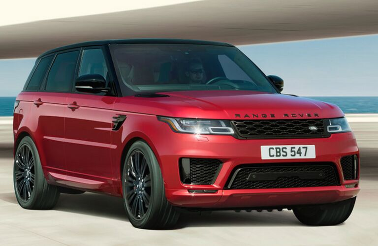 2018 Land Rover Range Rover Sport exterior shot red parked under a bridge next to a white beach and the ocean