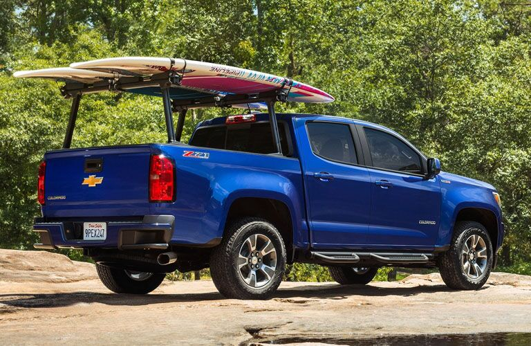 Blue 2019 Chevrolet Colorado with surfboard attached to rack over the bed