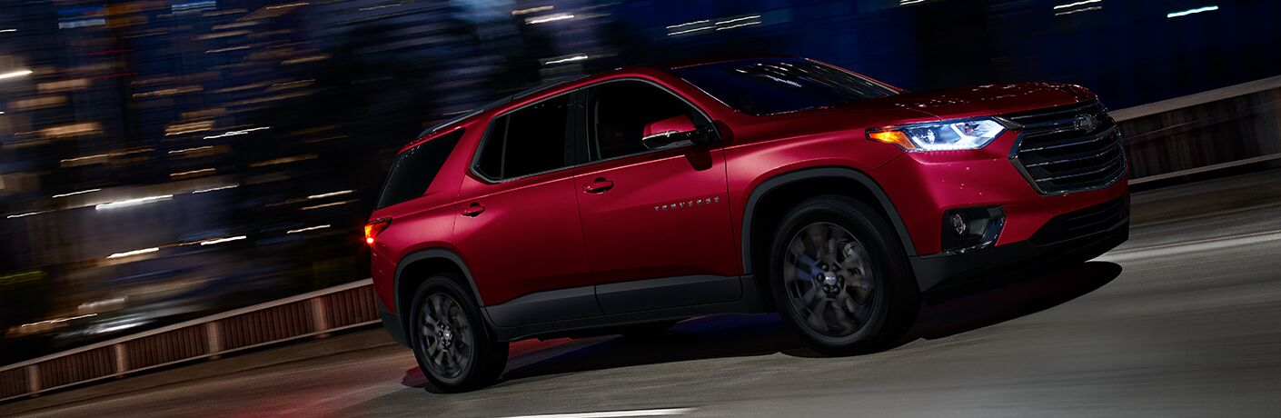 A red 2019 Chevrolet Traverse driving at night
