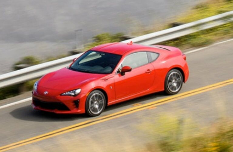 Exterior view of a red 2018 Toyota 86 driving down a country highway