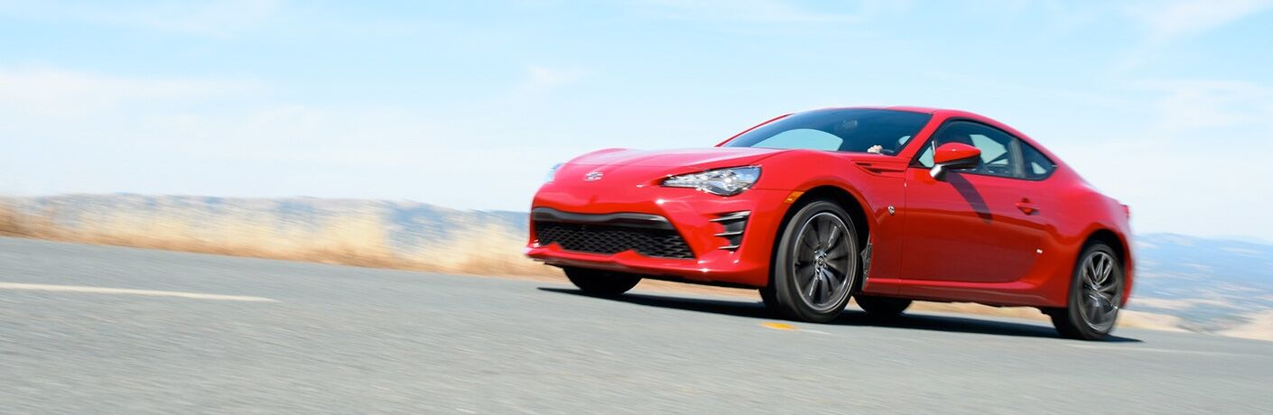 Exterior view of a red 2018 Toyota 86 driving down a country highway with mountains in the far background