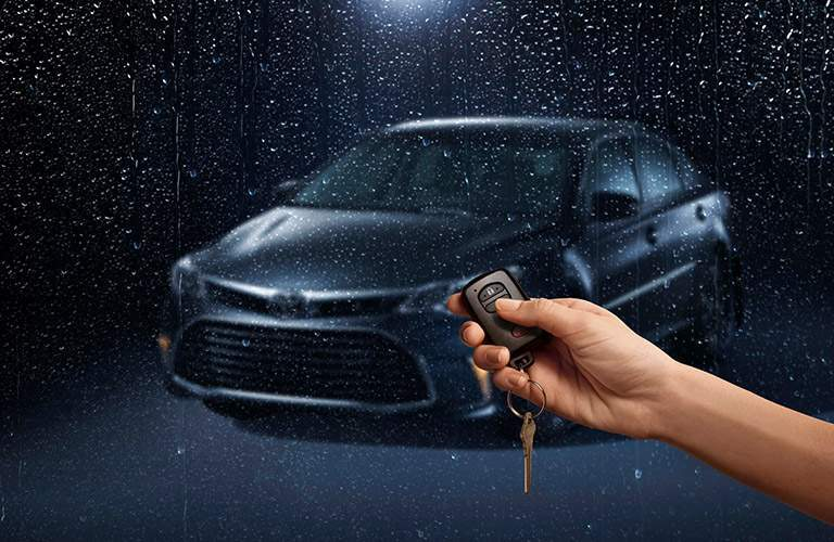 Hand holding car remote and view of 2018 Toyota Avalon Hybrid through rain-covered glass