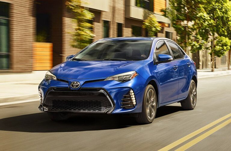 Exterior view of a blue 2019 Toyota Corolla driving down a city street