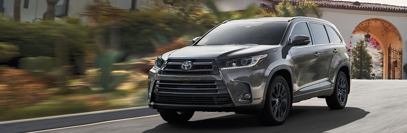 Black 2019 Toyota Highlander Driving Away from a Large White House