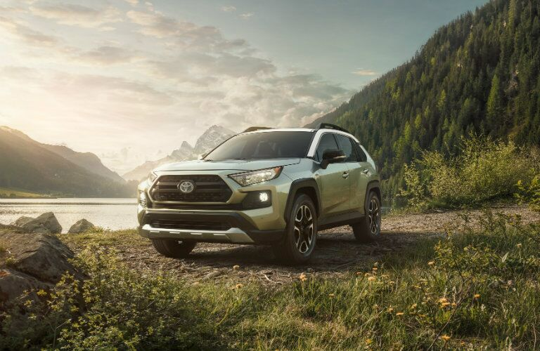 Exterior view of the front of a green 2019 Toyota RAV4 parked on a dirt path with a lake in the background