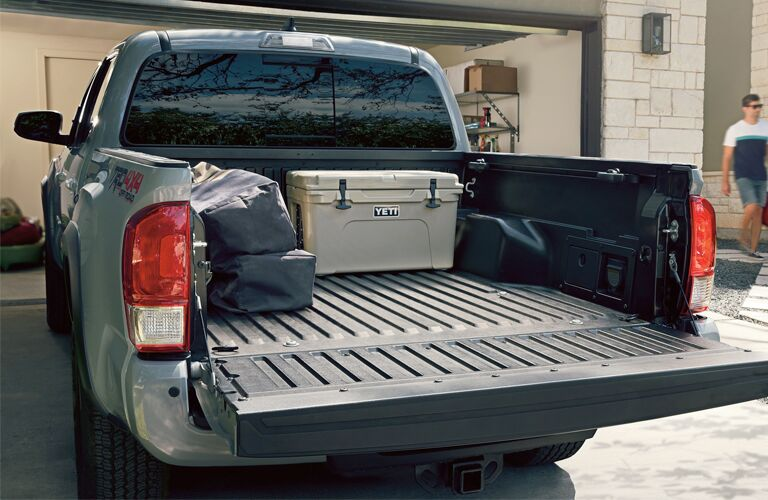 A storage container and bags in the bed of a 2019 Toyota Tacoma