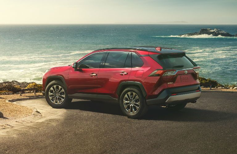Exterior view of the rear of a red 2019 Toyota RAV4 parked at the ocean shoreline