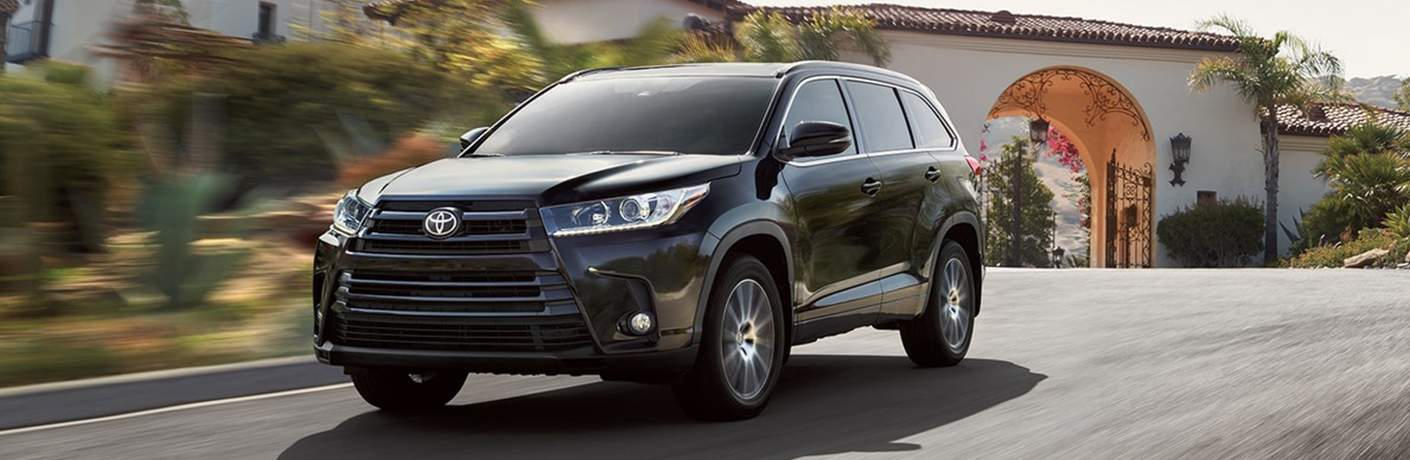 Black 2018 Toyota Highlander model driving down city street with archway in background